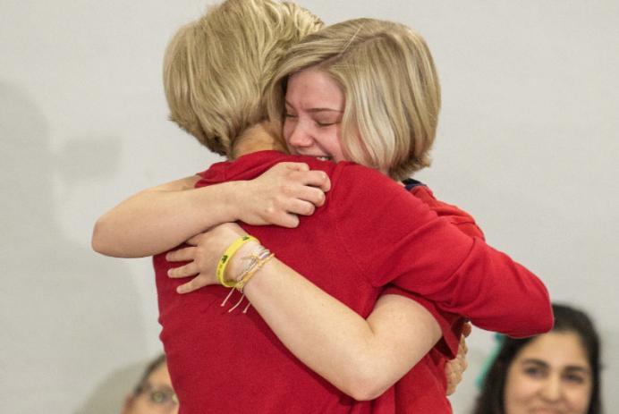 Elizabeth Warren hugs a supporter at a rally in Iowa