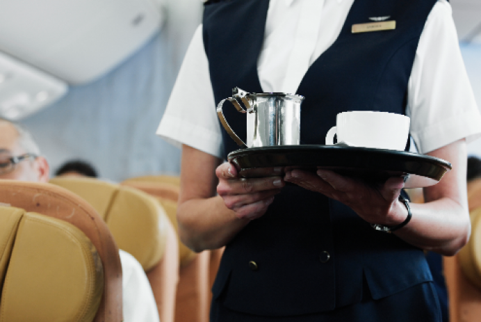 flight attendant carrying coffee down the aisle