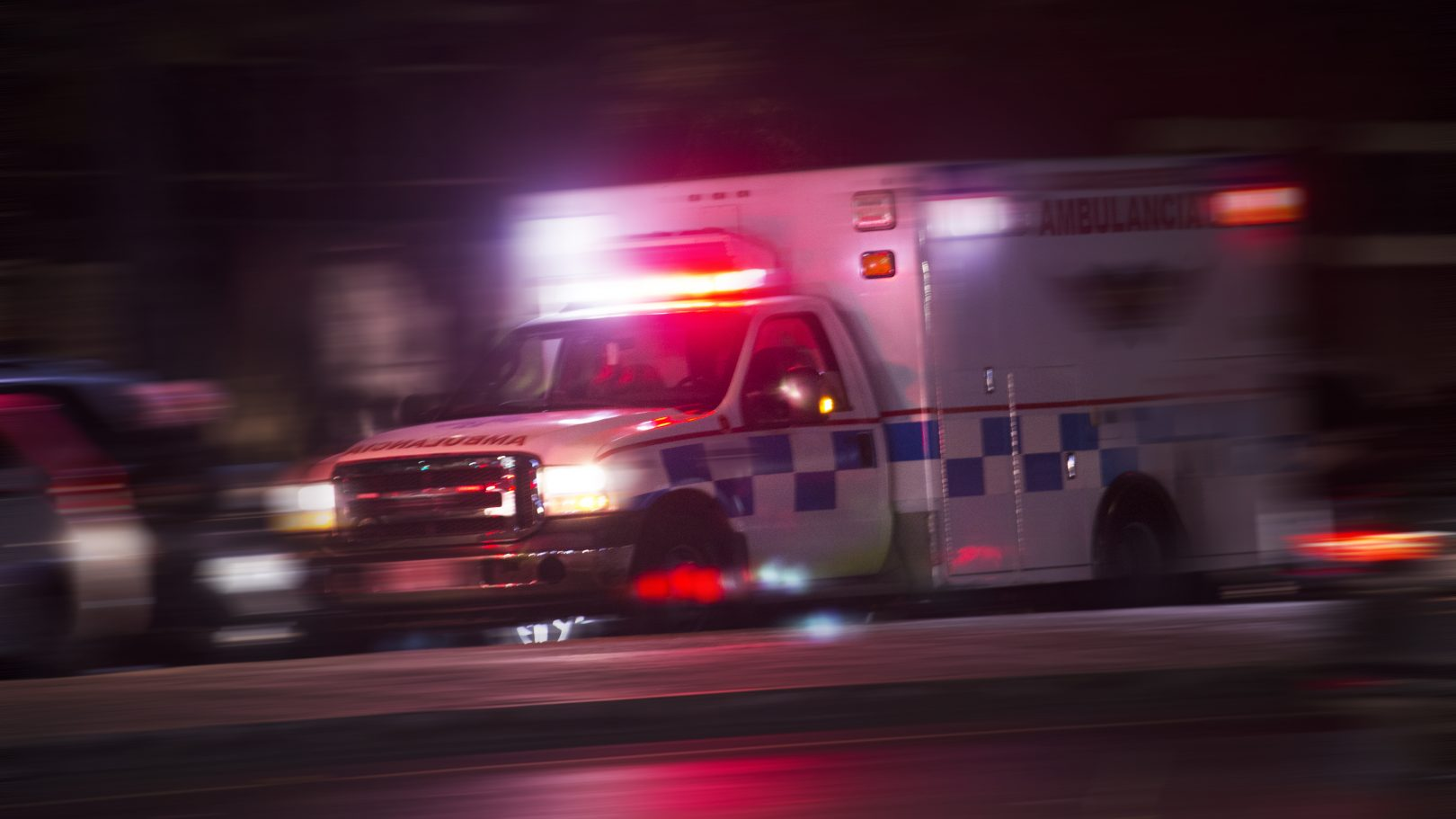 ambulance driving down street with sirens