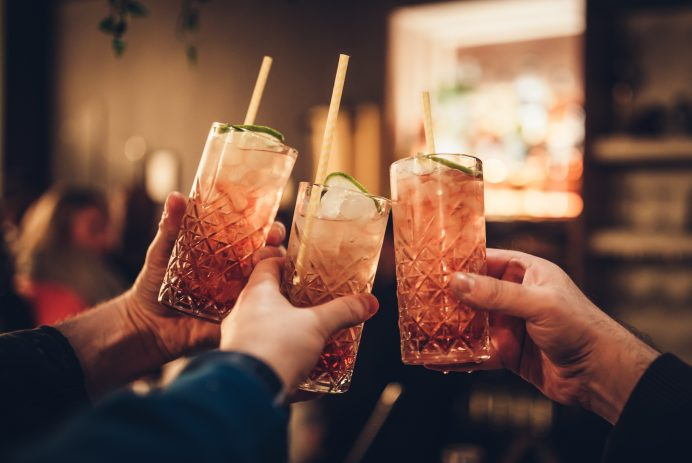three hands celebrating with drinks