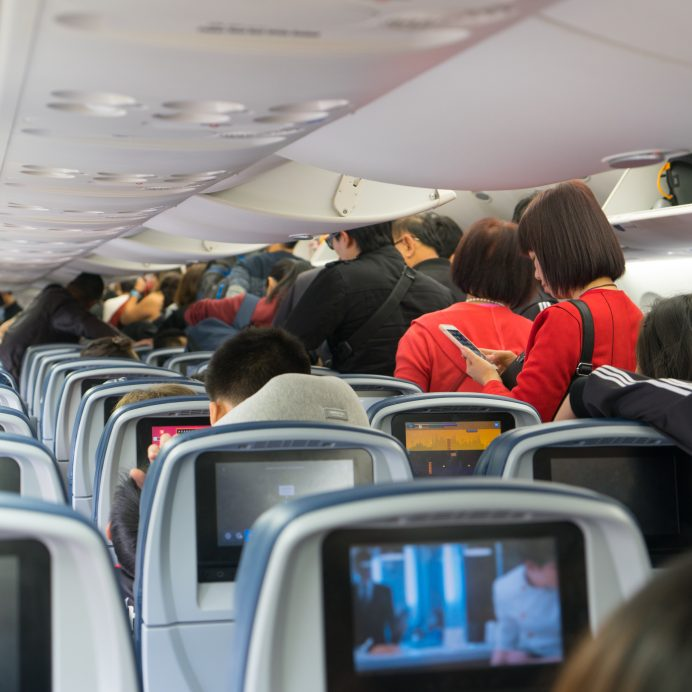 People are standing and sitting in an airplane cabin before disembarking.