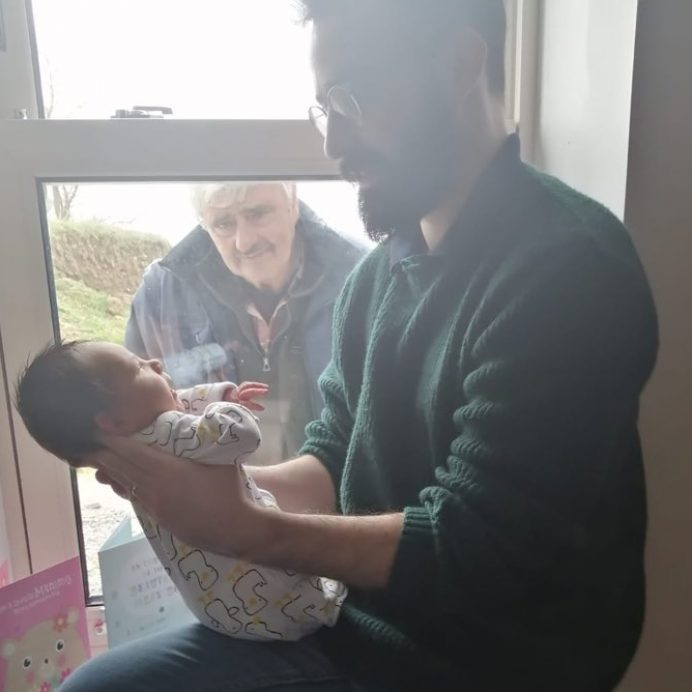 Man meeting grandson through window