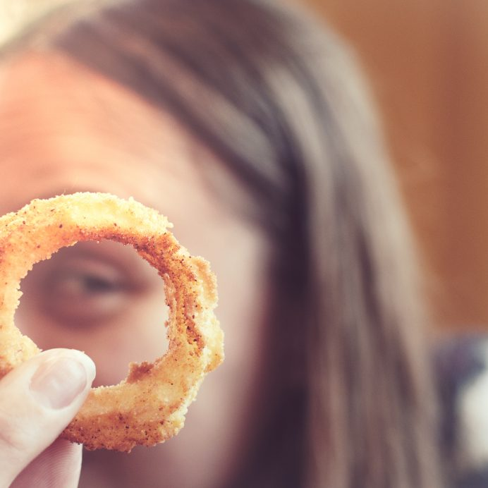 Close-Up Portrait Of Woman Holding Onion Ring
