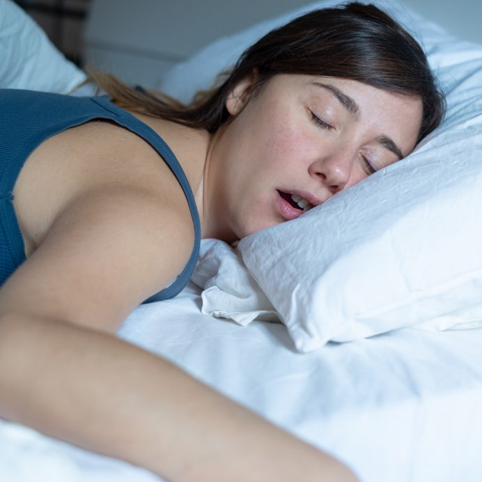 Face close up portrait of woman sleeping in bed and snoring