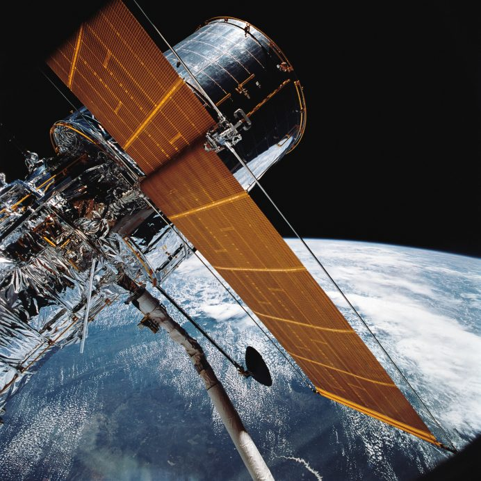 April 25, 1990 - The Hubble Space Telescope backdropped by planet Earth.