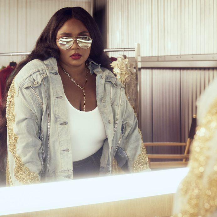Lizzo staring in a mirror with glasses on