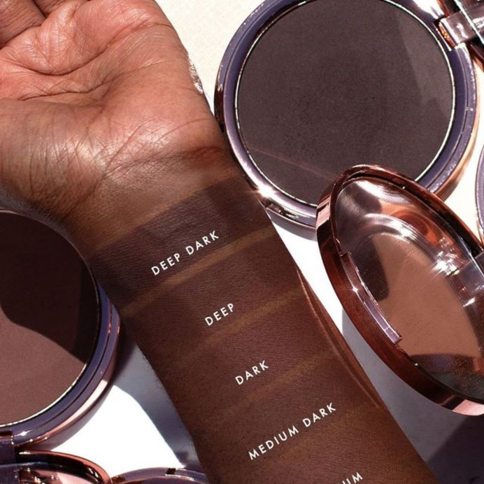 Brown skinned hand with bronzer swatches