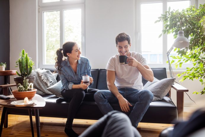 Cheerful young man and woman sitting on sofa in living room having coffee and talking
