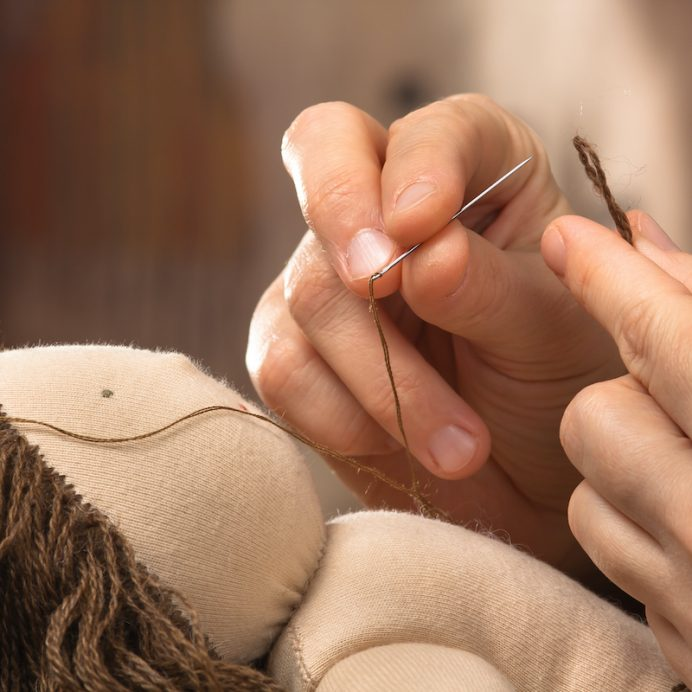 Closeup of hands sewing hair to the Waldorf doll