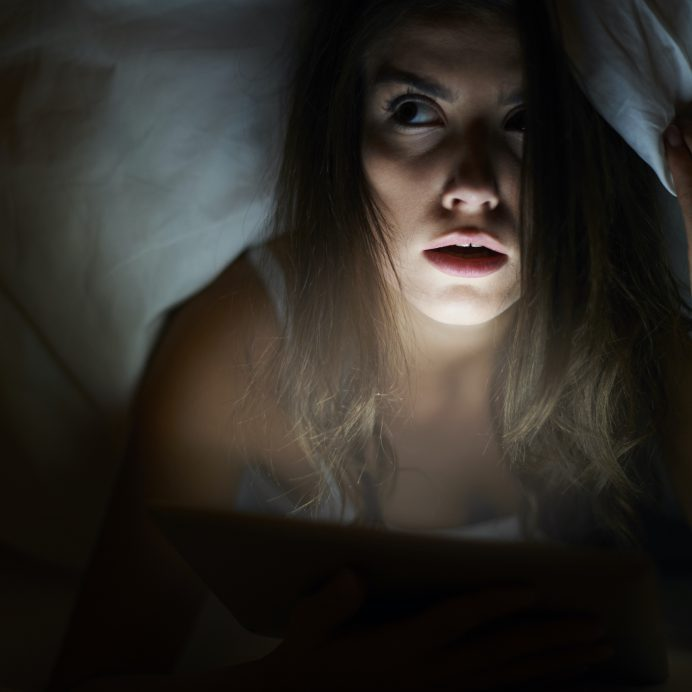 woman scared under covers paranormal activity ghost