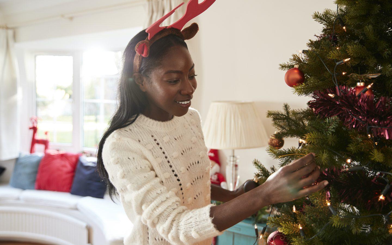 Woman decorating Christmas tree christmas decor hacks