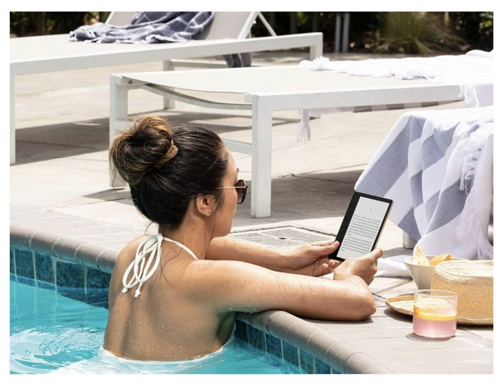 Woman reading on a waterproof Amazon Kindle in the pool while on vacation. Check out more Prime Day 2021 Kindle deals and deals on Kindle Unlimited.